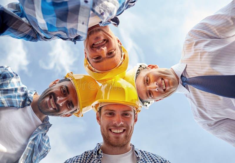 Sluit omhoog van bouwers die bouwvakkers in cirkel dragen stock fotografie