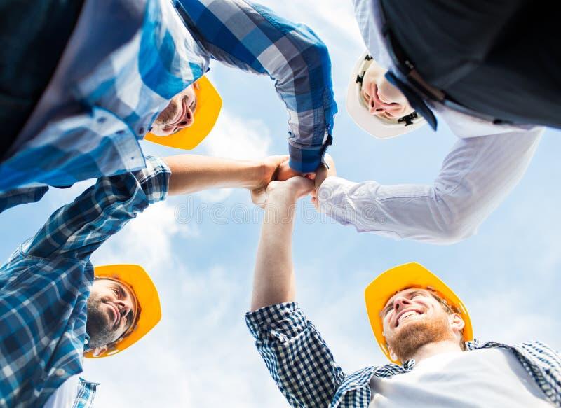 Sluit omhoog van bouwers die in bouwvakkers hoge vijf maken royalty-vrije stock afbeeldingen