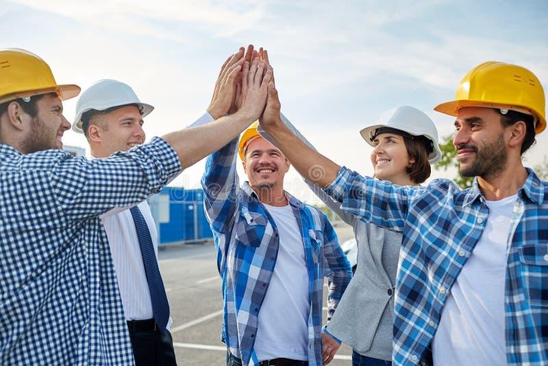 Sluit omhoog van bouwers die in bouwvakkers hoge vijf maken stock foto