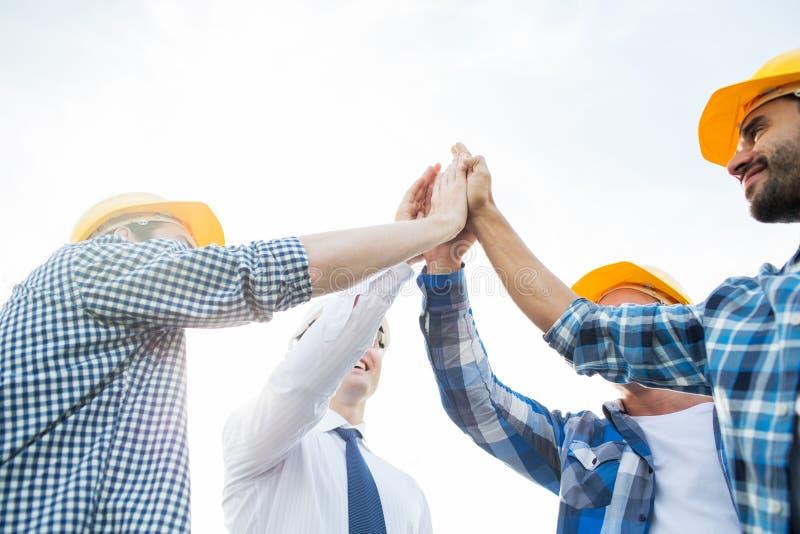 Sluit omhoog van bouwers die in bouwvakkers hoge vijf maken stock foto's