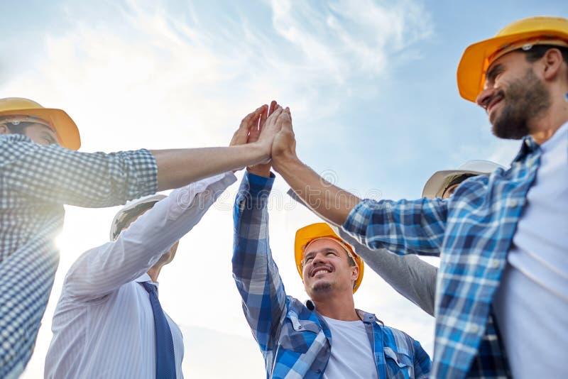 Sluit omhoog van bouwers die in bouwvakkers hoge vijf maken stock afbeelding