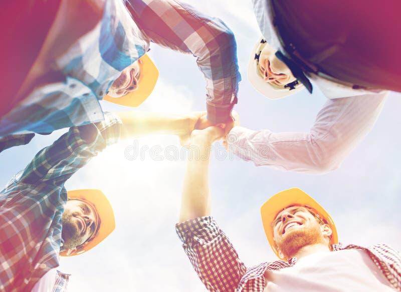 Sluit omhoog van bouwers die in bouwvakkers hoge vijf maken stock fotografie