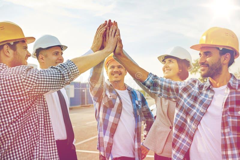 Sluit omhoog van bouwers die in bouwvakkers hoge vijf maken royalty-vrije stock fotografie