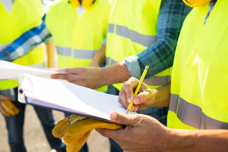 Sluit omhoog van bouwers die in vesten aan klembord schrijven royalty-vrije stock foto