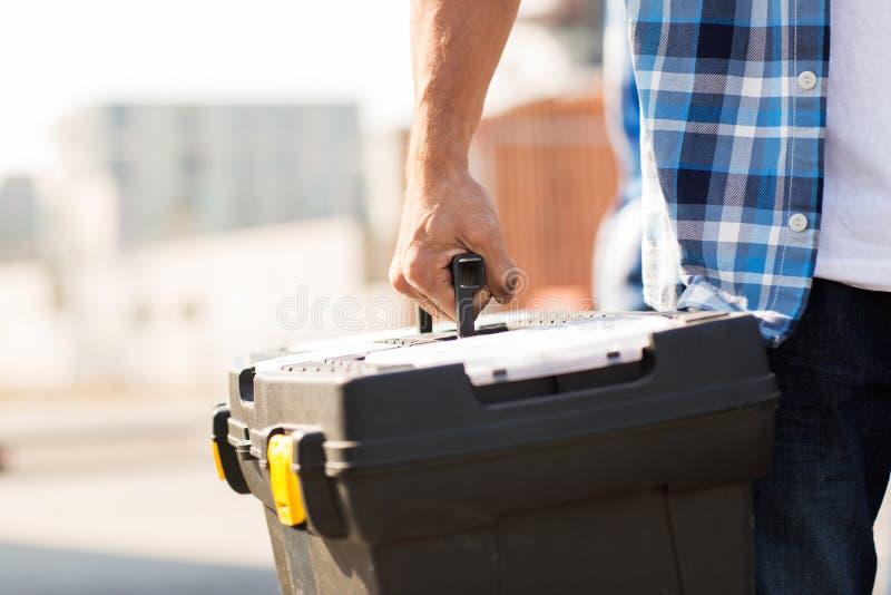 Sluit omhoog van bouwers dragende toolbox in openlucht stock foto's