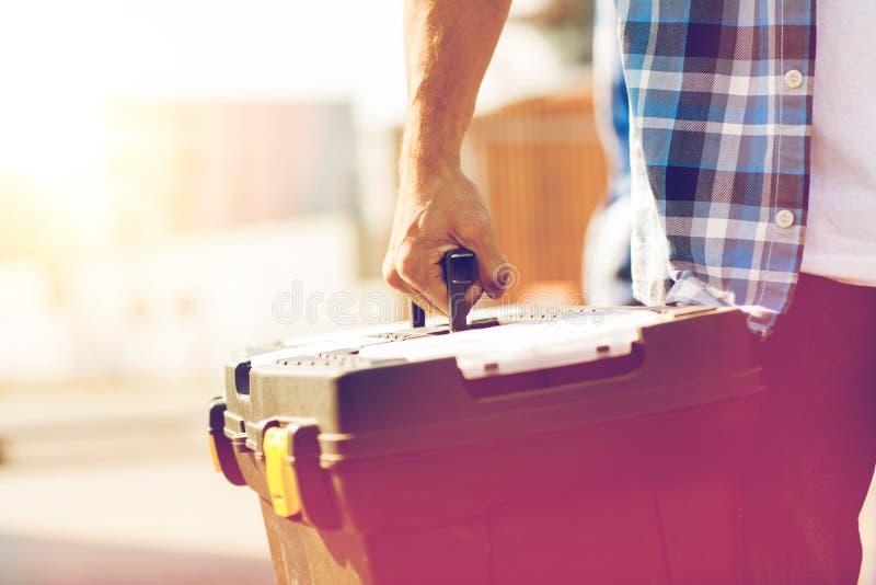 Sluit omhoog van bouwers dragende toolbox in openlucht stock foto