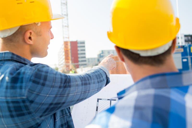 Sluit omhoog van bouwers met blauwdruk bij de bouw stock afbeeldingen
