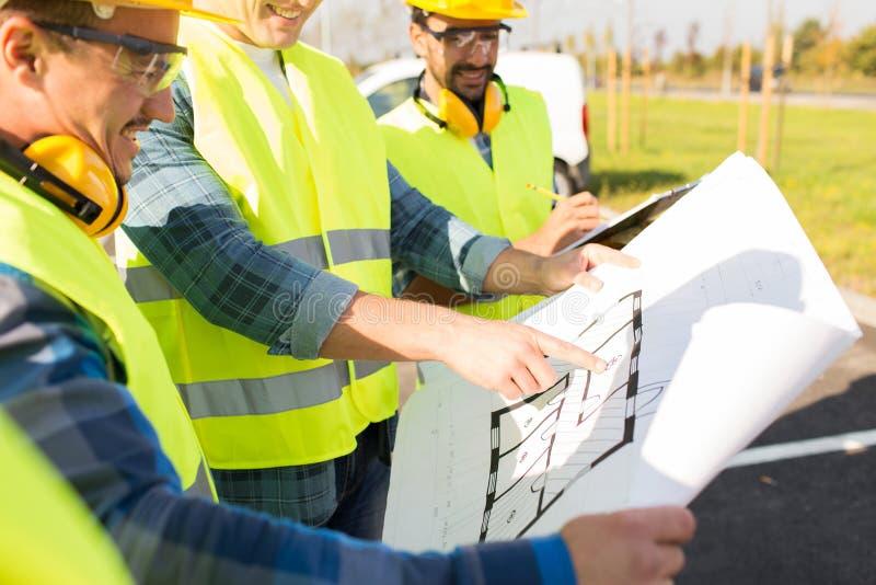 Sluit omhoog van bouwers met blauwdruk bij de bouw stock fotografie