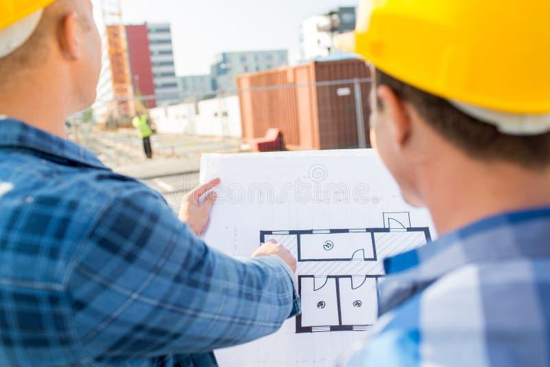 Sluit omhoog van bouwers met blauwdruk bij de bouw stock foto's