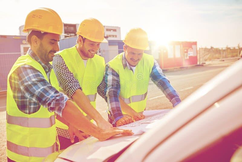 Sluit omhoog van bouwers met blauwdruk op autokap royalty-vrije stock foto
