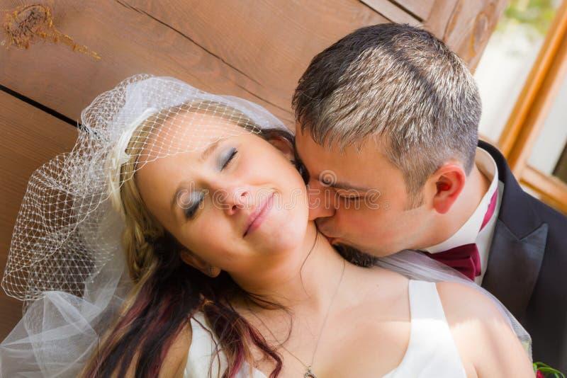 Sluit omhoog van bruidegom die de bruid kust stock afbeelding