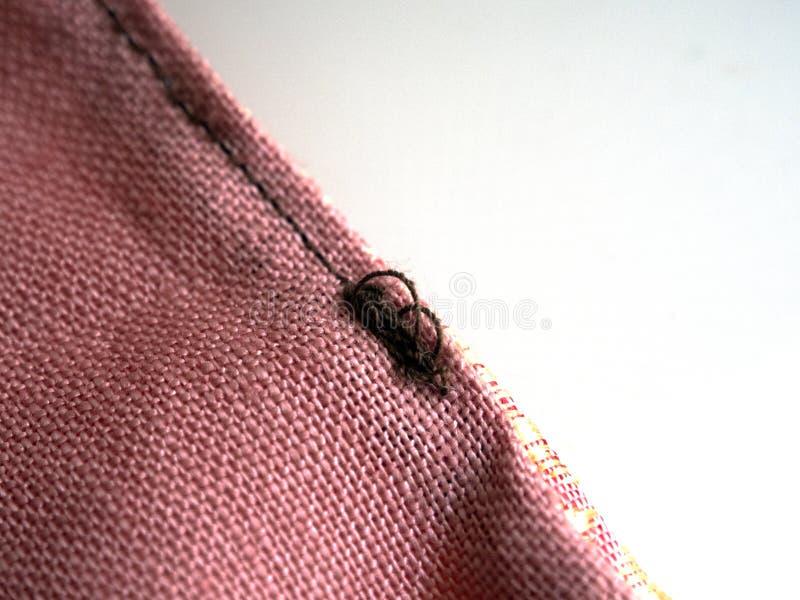 Sluit omhoog van bruine draadknoop op de roze-oranje textuur van de linnenstof met exemplaarruimte Materialen, textiel en kleding royalty-vrije stock afbeeldingen