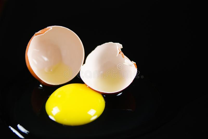 Sluit omhoog van bruine gebarsten eishell met ruwe gele yalk en slijmerig eiwit bij het wijzen van op glanzende zwarte achtergron stock afbeelding