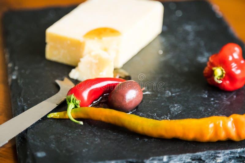 Sluit omhoog van cheddarkaas, Spaanse peper en olijf op lei royalty-vrije stock afbeeldingen