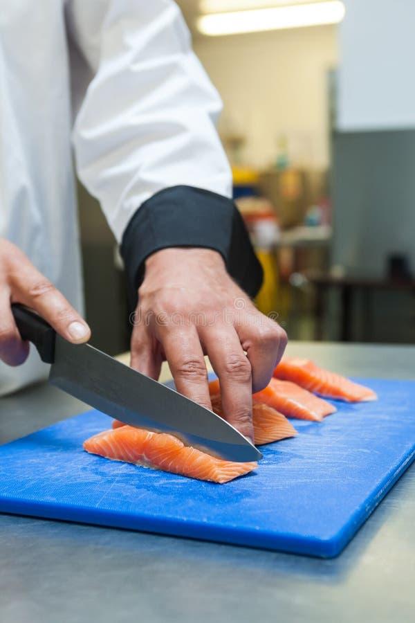 Sluit omhoog van chef-kok die ruwe zalm met scherp mes snijden royalty-vrije stock afbeelding