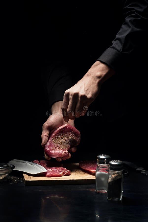 Sluit omhoog van chef-kokshanden die het vlees kruiden stock afbeelding