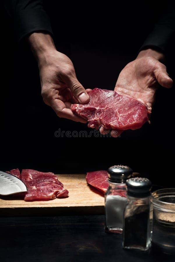 Sluit omhoog van chef-kokshanden houdend vlees stock afbeelding