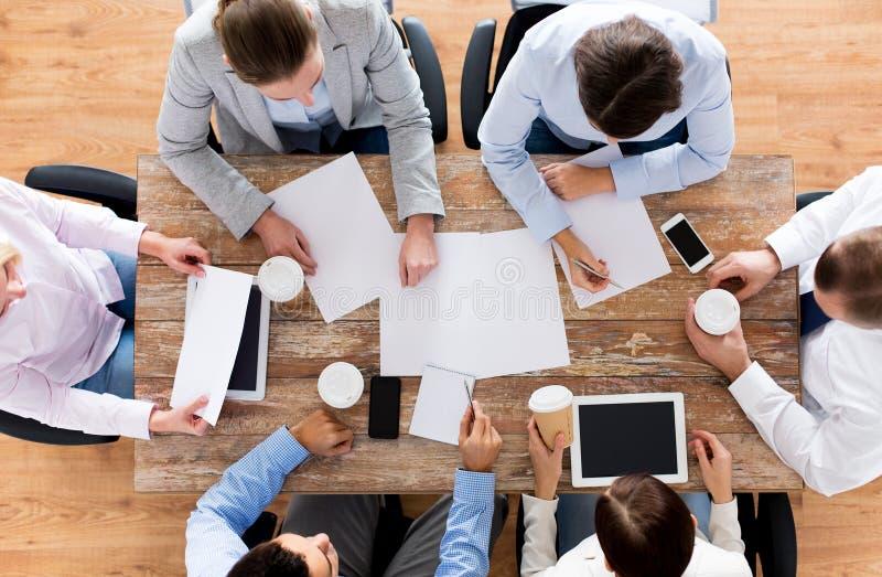 Sluit omhoog van commercieel team met koffie en documenten stock fotografie