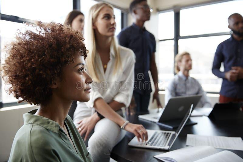 Sluit omhoog van creatieve bedrijfscollega's die aan een informele presentatie in een vergaderzaal luisteren royalty-vrije stock fotografie