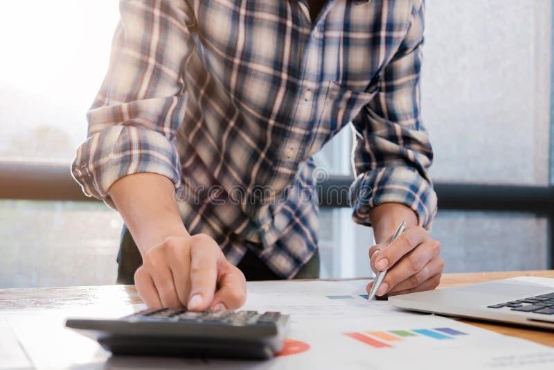 Sluit omhoog van de accountantsmens of bankier die berekeningen en overlapping maken stock foto's