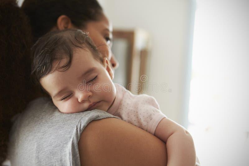 Sluit omhoog van de Babydochter van de Moeder Knuffelende Slaap thuis royalty-vrije stock afbeelding