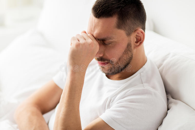 Sluit omhoog van de beklemtoonde mens in bed thuis royalty-vrije stock afbeelding