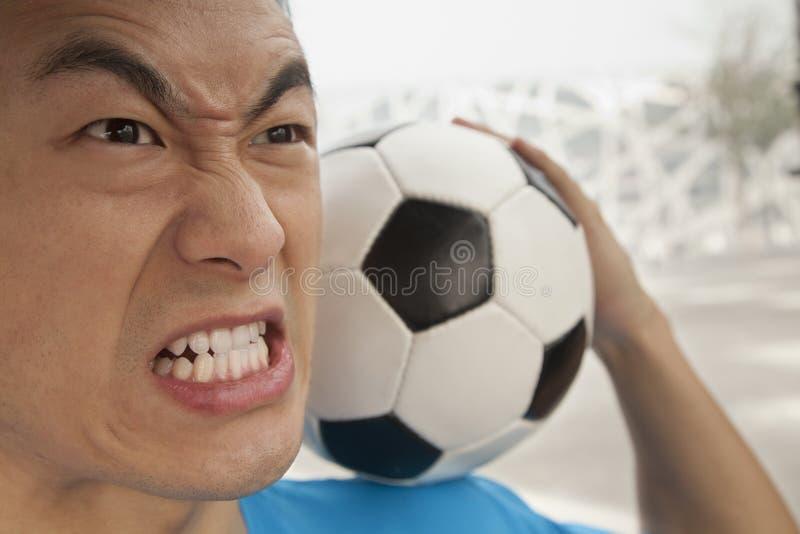 Sluit omhoog van de boze jonge mens die een voetbalbal op zijn schouder houden royalty-vrije stock foto's