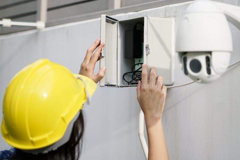 Sluit omhoog van de Camera van kabeltelevisie van Fixing van de vrouwentechnicus op Muur stock afbeelding