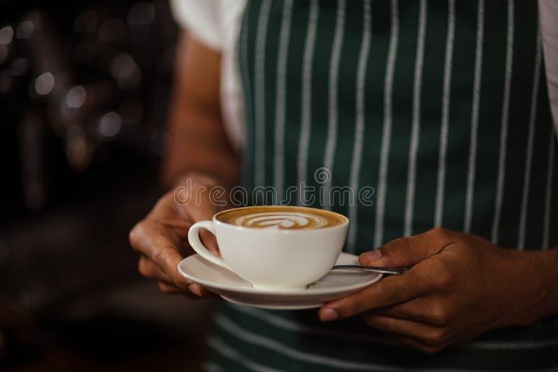 Sluit omhoog van de cappuccino van de baristaholding royalty-vrije stock afbeeldingen