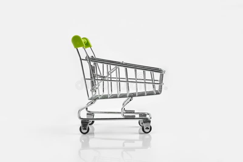 Sluit omhoog van de duwkar van de supermarktkruidenierswinkel voor het winkelen met zwarte wielen op witte achtergrond Concept he stock afbeeldingen
