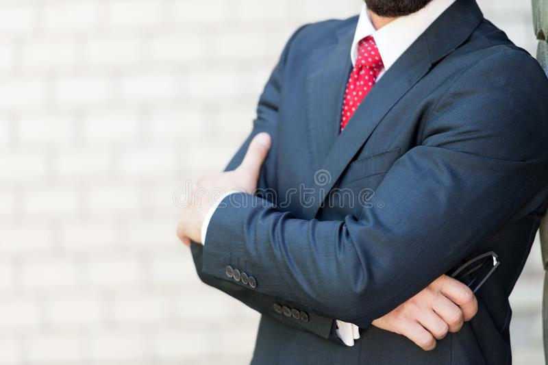 Sluit omhoog van de elegante mens die zich met zijn gekruiste wapens bevinden royalty-vrije stock afbeeldingen