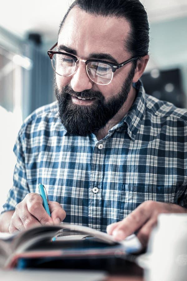 Sluit omhoog van de gebaarde donker-haired pen van de zakenmanholding en het maken van nota's stock afbeelding