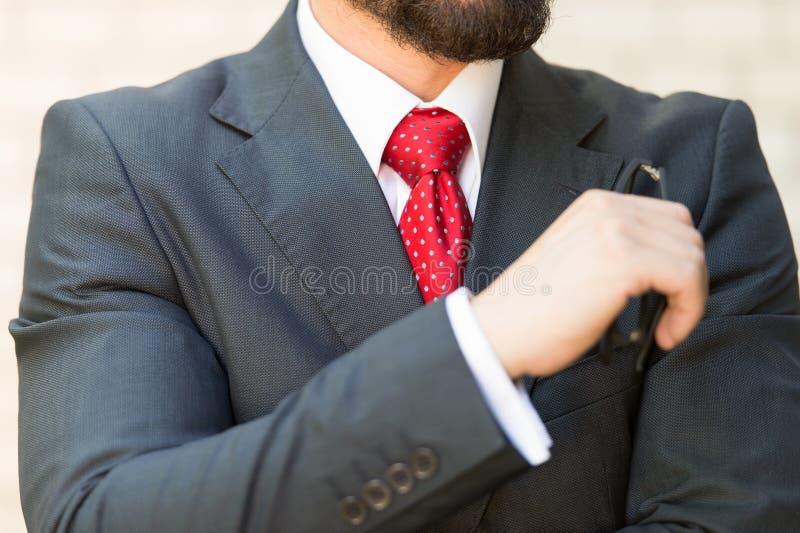Sluit omhoog van de gebaarde mens die in elegant kostuum zijn glazen houden royalty-vrije stock foto
