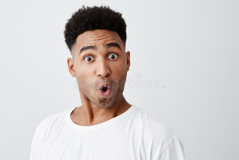 Sluit omhoog van de grappige knappe jonge donker-gevilde mens die met afrokapsel in modieuze witte t-shirt in camera met kijken stock fotografie