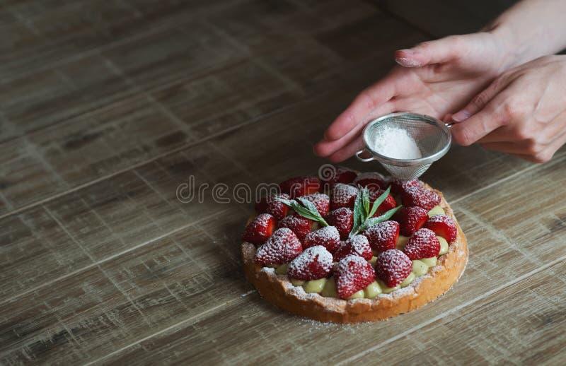 Sluit omhoog van de hand van de vrouwelijke gebakjechef-kok verfraaiend bovenkant van delicio stock foto's