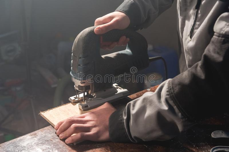 Sluit omhoog van de handen die van de timmerman machtshulpmiddelen om hout werken te verwerken Machtsfiguurzaag stock fotografie