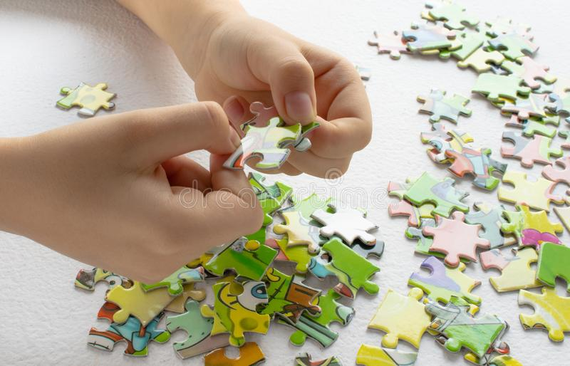Sluit omhoog van de handen van het kind spelend met kleurrijke raadsels op lichte lijst Vroeg lerend stock foto