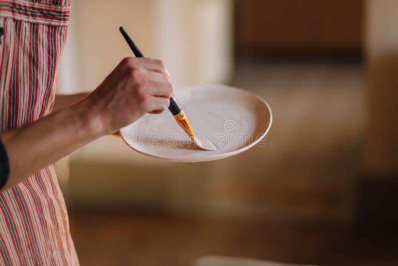 Sluit omhoog van de handen van de pottenbakker makend ornament op ceramisch product Plaat in de handen van het mannetje Jonge kun royalty-vrije stock foto's