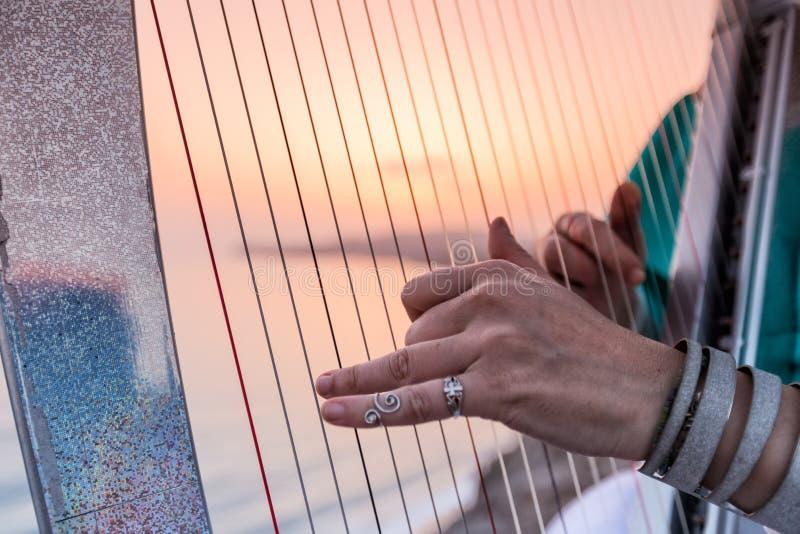 Sluit omhoog van de handen van vrouw het spelen harp door het overzees bij zonsondergang royalty-vrije stock afbeeldingen