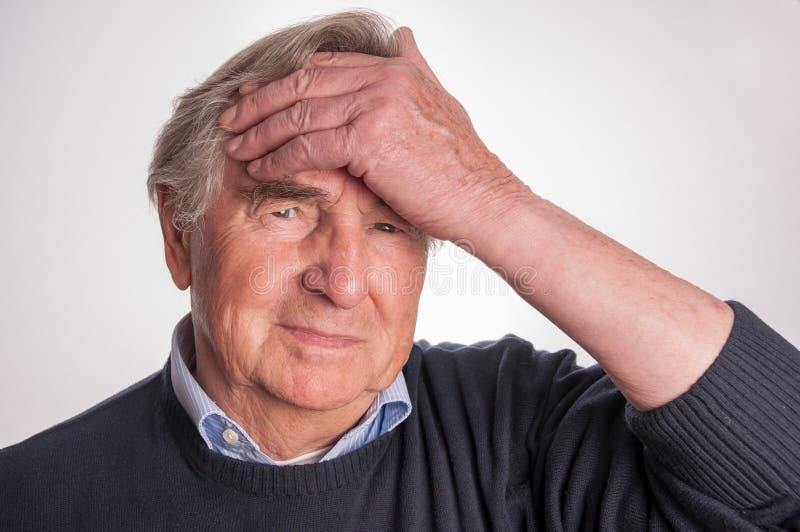 Sluit omhoog van de hogere die mens met hoofdpijn op witte achtergrond wordt geïsoleerd royalty-vrije stock fotografie