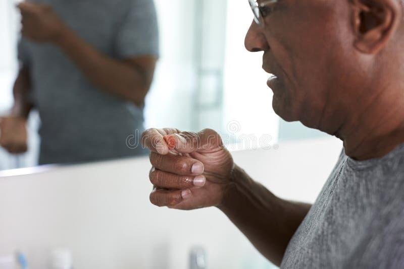 Sluit omhoog van de Hogere Mens in Badkamersspiegel die Pyjama's dragen die de Tablet van het Vitaminesupplement nemen royalty-vrije stock afbeelding