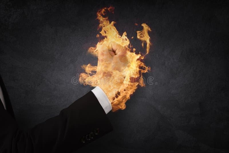 Sluit omhoog van de holdingsbrand van de zakenmanhand in vuist stock fotografie