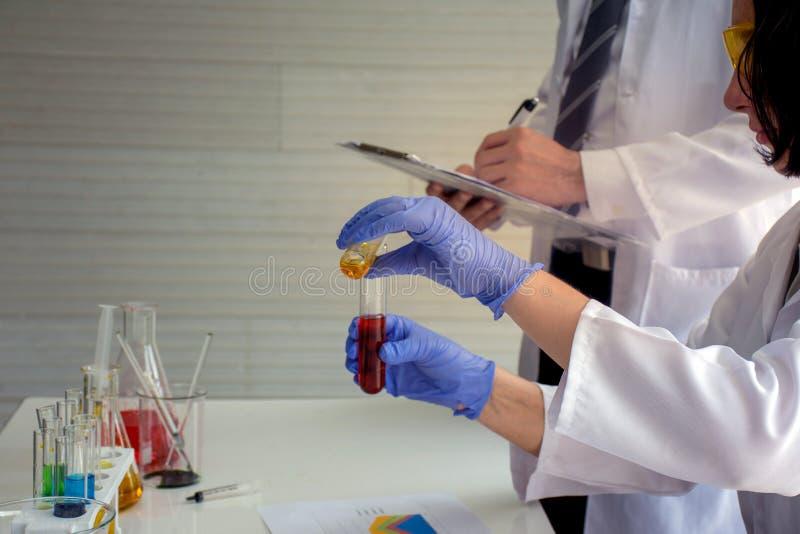 Sluit omhoog van de holdingsbuis van de wetenschapperchemicus met een rode vloeibare chemische oplossing die test of onderzoek ma stock fotografie