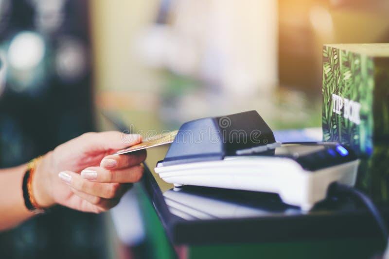 Sluit omhoog van de holdingscreditcard van de vrouwenhand bij de supermarkt CH stock fotografie