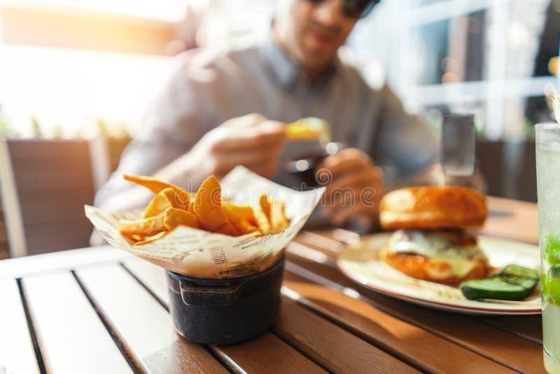 Sluit omhoog van de jonge aantrekkelijke mens die frieten en hamburger eten bij straatkoffie stock afbeeldingen