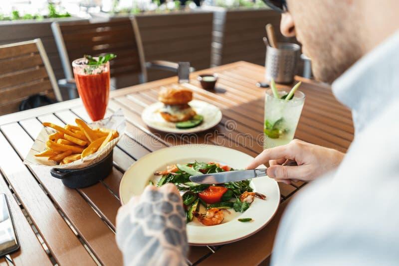 Sluit omhoog van de jonge aantrekkelijke mens die salade eten bij straatkoffie Achter mening stock fotografie