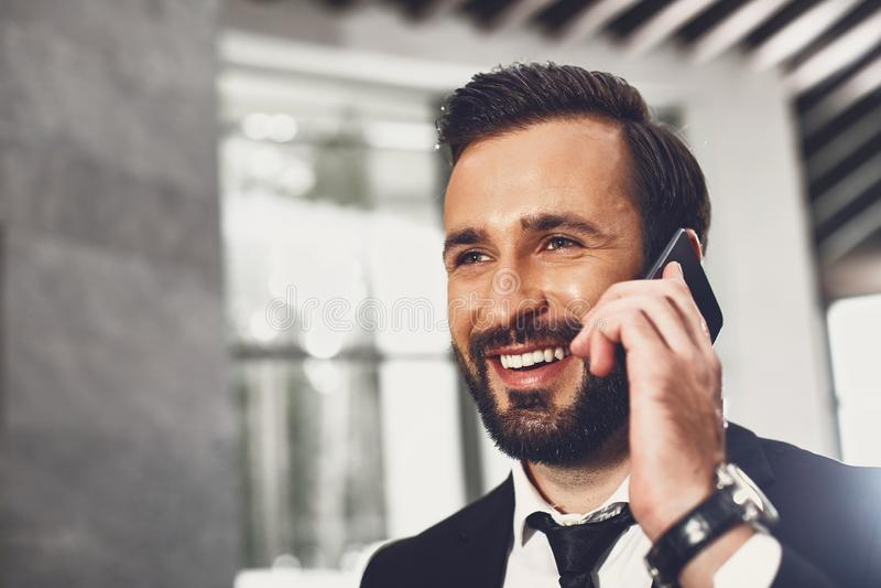 Sluit omhoog van de knappe jonge mens die op de telefoon en het glimlachen spreken stock afbeelding
