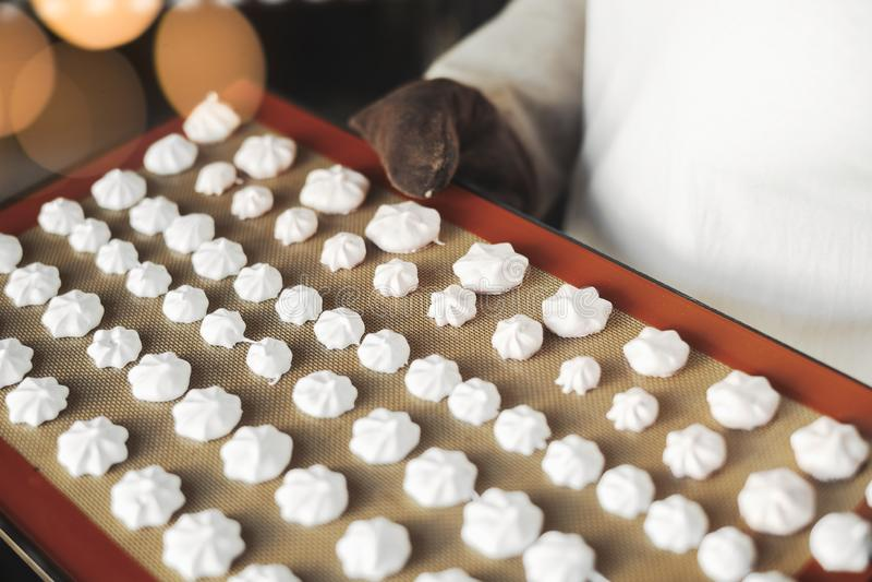 Sluit omhoog van de koekjes van het de pastelkleurschuimgebakje van de kokholding op ovendienblad royalty-vrije stock afbeelding