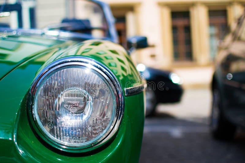 Sluit omhoog van de koplamp van een groene klassieke sportwagen, met vage achtergrond royalty-vrije stock foto's