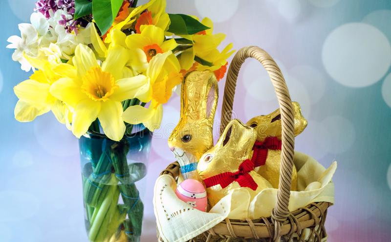 Sluit omhoog van de lentebloemen en de in folie verpakte konijnen van Pasen royalty-vrije stock afbeelding